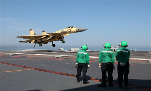 A J-15 fighter jet prepares to land on the carrier, the Liaoning, during the 25-day test and training session, which concluded on Wednesday. Photo: CFP