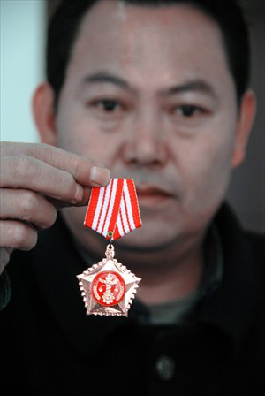 Cai Guojun, director of the court of Jinzhong township in Weining, shows his badge of office. Photo: CFP