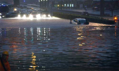 A car is submerged at Lianhua Bridge in Beijing, capital of China, July 21, 2012. A downpour hit the city on Saturday. Local meteorologic authority issued an orange alarm against heavy rains at 6:30 pm. Photo: Xinhua