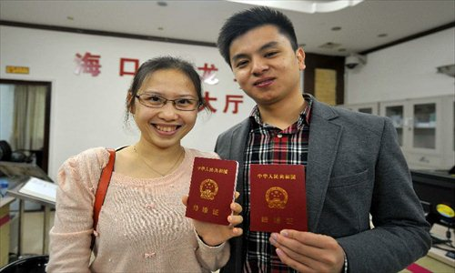 A couple show their marriage certificates at the marriage registration office in Haikou, capital of South China's Hainan Province, January 4, 2013. Quite a number of couples flocked to tie the knot on January 4, 2013, or 2013/1/4, which sounds like