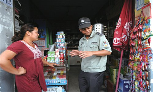 A foreign chengguan volunteer talks to a local shopowner.