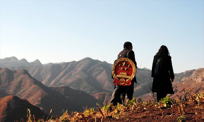 Two judicial workers, one carrying the national emblem on his back, walk along a mountain path. Photo: CFP