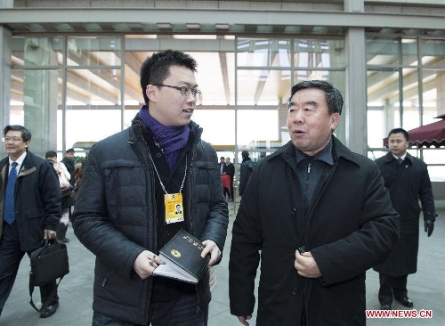 Fu Kecheng (R front), a member of the 12th National Committee of the Chinese People's Political Consultative Conference (CPPCC) from east China's Jiangxi Province, receives an interview upon his arrival in Beijing, capital of China, March 1, 2013. The first session of the 12th CPPCC National Committee will open on March 3. (Xinhua/Wang Ye)