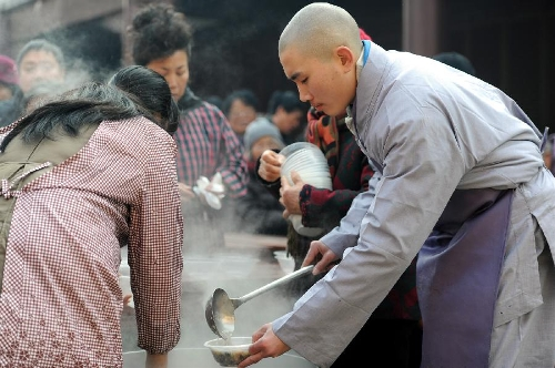 A monk distributes porridge to citizens at the Pilu Temple in Nanjing, capital of east China's Jiangsu Province, Jan. 19, 2013, to celebrate the traditional Laba Festival. Laba literally means the eighth day of the 12th lunar month. The Laba Festival is regarded as a prelude to the Spring Festival, or Chinese Lunar New Year, the most important occasion of family reunion, which falls on Feb. 10 this year. Eating porridge is an old tradition on the Laba Festival in China. Many temples also have the tradition of offering porridge to the public to commemorate Buddha and deliver his blessings to both believers and non-believers. (Xinhua/Han Yuqing)