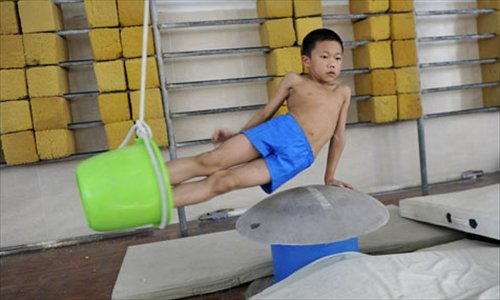 A boy trains with the help of a bucket in Zhangshan Sports School in Guangdong Province.