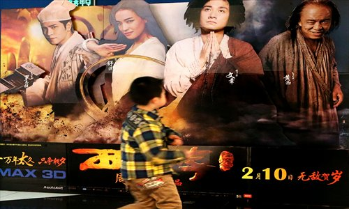 A boy passes a poster for the film Journey to the West: Conquering the Demons at a cinema in Shanghai Monday. Photo: Yang Hui/GT