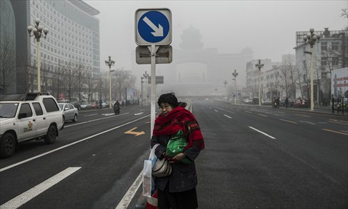 A citizen waits to cross a smoggy street in Beijing, the capital of China, on January 29, 2013. The National Meteorological Center (NMC) issued a code-blue alert on January 27 as the smoggy weather forecast for the following two days would cut visibility and worsen air pollution in some central and eastern Chinese cities. Photo: Li Hao/GT
