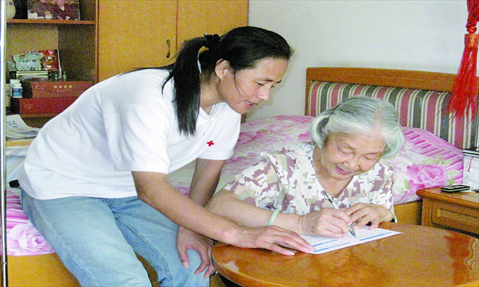 With the help of Gao Min (left), a professional organ donation coordinator, Liu Youxue fills out a form to donate her husband's corneas and body in Shenzhen on August 25, 2010. Liu's husband died a year later at the age of 92. Photo: Courtesy of Gao Min