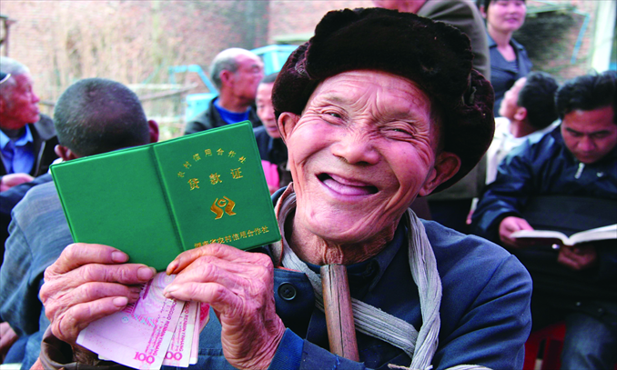 Zhao Chengrong, an elderly farmer from Wufeng township, Hunan Province, is happy to get a preferential loan of 500 yuan to prepare for the coming spring ploughing on March 2, 2011. Photo: IC
