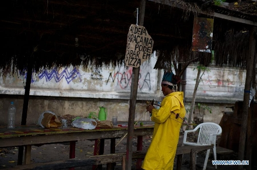 An Indigenous man sharpens an arrow at the old Indian Museum in Rio de Janeiro,Brazil, Jan. 16, 2013. The government of Rio de Janeiro plans to tear down an old Indian museum beside Maracana Stadium to build parking lot and shopping center here for the upcoming Brazil 2014 FIFA World Cup. The plan met with protest from the indigenous groups. Now Indians from 17 tribes around Brazil settle down in the old building, appealing for the protection of the century-old museum, the oldest Indian museum in Latin America. They hope the government could help renovate it and make part of it a college for indigenous Indians. (Xinhua/Weng Xinyang)