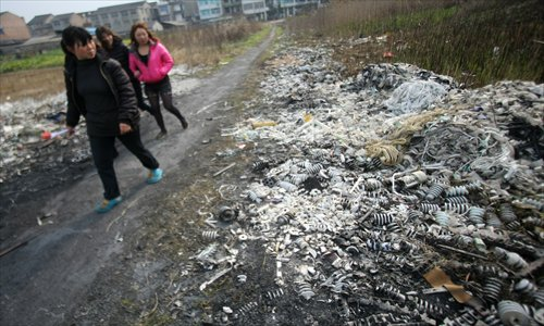 People pass a battery factory in Luqiao district, Taizhou, Zhejiang Province, on March 24, 2011. The factory discharged pollutants into the soil, which led to serious contamination of the surrounding water and resulted in hundreds of people having elevated levels of lead in their blood. Photo: IC