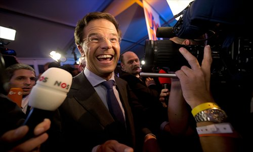 Netherlands' Prime Minister and conservative-liberal party VVD leader Mark Rutte smiles in front of the media at the Carlton Beach Hotel in Scheveningen, The Hague on Wednesday, where he gathered with his party to await the country's general election results. Photo: AFP