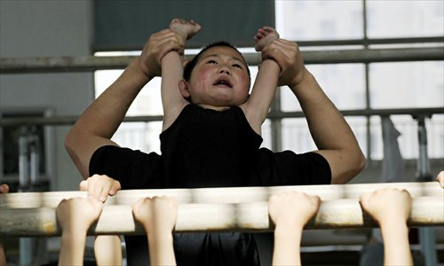 A boy stretches his back with the help of a coach at the Jiaxing Children's Sports School in Jiaxing, Zhejiang Province. Photos: ifeng.com