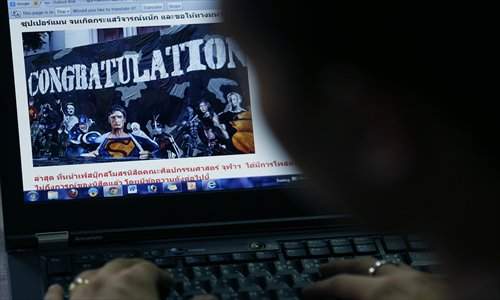 A Thai person looks at a website displaying a picture of a mural on campus depicting Adolf Hitler along with several comic book heroes inside, in Bangkok on July 16. Photo: CFP