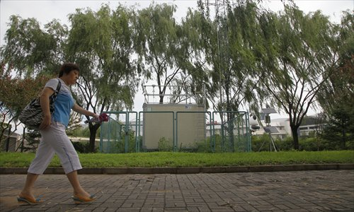 A resident walks past an air quality monitoring station set up in the Olympic Green, Beijing. Photo: CFP