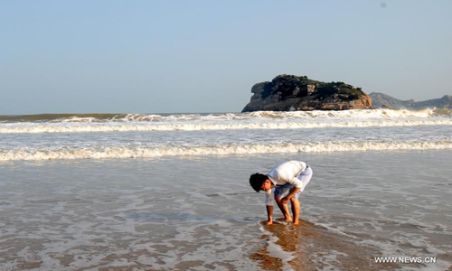A tourist plays on the beach of the Nanji Island, east China's Zhejiang Province, October 14, 2012. The 7.64-square kilometer Nanji Island, as the largest island of the Nanji Islands, was named for its muntjac shape. The archipelago were listed as China's first level-five marine nature reserve in 1990. Photo: Xinhua