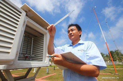 An engineer of the local meteorological authority tests the air temperature in Sansha City, south China's Hainan Province, May 21, 2013. (Xinhua/Zha Chunming)