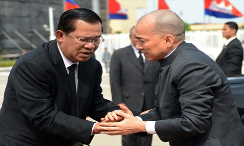 Cambodian King Norodom Sihamoni (R) shakes hands with Prime Minister Hun Sen (L) before departing for China at Phnom Penh International airport on Monday. Cambodia's former king Norodom Sihanouk, whose life mirrored the turbulent history of his nation where he remained a revered figure, died in Beijing on Sunday. Photo: AFP