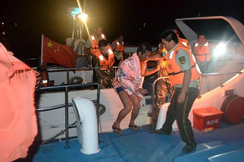 Local officers help a fisherman escape from a fishing boat which is on fire in the sea area of Dongchongkou in Ningde, East China's Fujian Province, July 30, 2012. Seven fishermen in the boat were rescued. One of them suffering from severe fire burn was sent to hospital. Photo: Xinhua