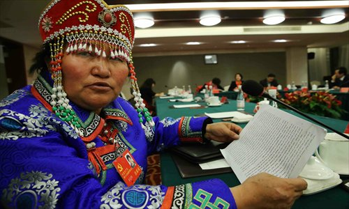 A delegate to the 18th Party congress from a minority ethnic group in Qinghai Province shows her speech in Mongolian Sunday. Photo: Xinhua