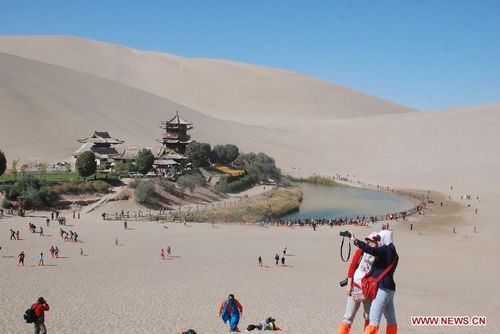 Tourists visit the Yueyaquan scenic zone in Dunhuang, Northwest China's Gansu Province, October 4, 2012. China's