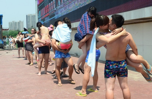 More than 20 couples participate in a romantic kissing competition held in Happy Magic Water Cube, a large-scaled water park in Beijing's Fengtai District, on July 6, 2013, the International Kissing Day. (Photo: china.org.cn / gmw.cn)