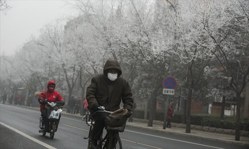 People ride along a Smog-shrouded street in Beijing, the capital of China, on January 29, 2013. The National Meteorological Center (NMC) issued a code-blue alert on January 27 as the smoggy weather forecast for the following two days would cut visibility and worsen air pollution in some central and eastern Chinese cities. Photo: Li Hao/GT
