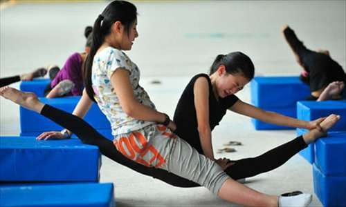 A coach sits on a girl's thigh during splits stretches at the Shenyang sports school in Liaoning Province. About 60 students from 6 to 15 years old train here, the best of which continue on to the national team.
