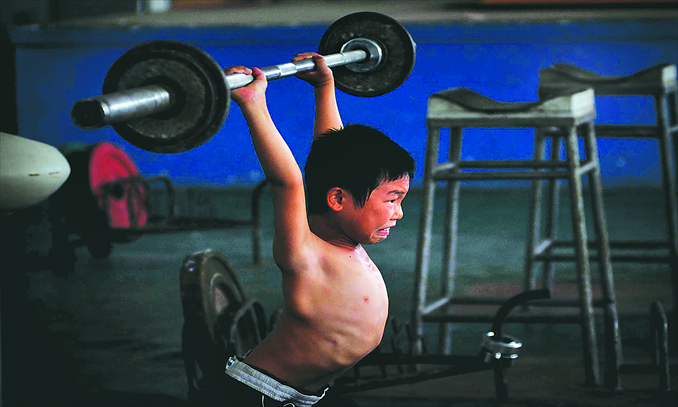 Main: A boy practises weightlifting in Xiamen Sports School, now the Xiamen Competitive Sports Management Center. Photo: CFP
