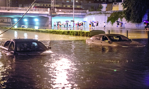 Two cars are inundated in the water near Lianhua bridge in southern Beijing early on Sunday, after the heaviest rainstorm in 61 years hit the capital on Saturday. Photo: Li Hao/GT