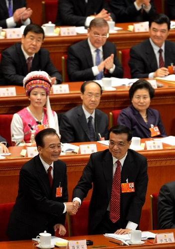 Wen Jiabao (L bottom) shakes hands with Li Keqiang after he delivered the government work report during the opening meeting of the first session of the 12th National People's Congress (NPC) at the Great Hall of the People in Beijing, capital of China, March 5, 2013. The first session of the 12th NPC opened in Beijing on March 5. (Xinhua/Wang Song)