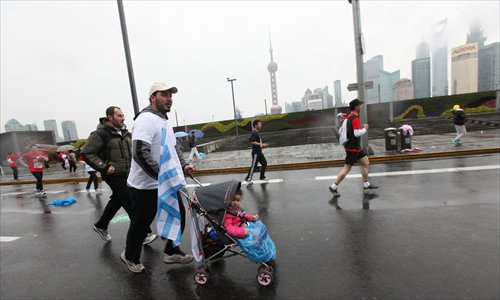 A runner pushes a child in a stroller during the annual Shanghai International Marathon on December 2. More than 30,000 runners participated in the annual Shanghai International Marathon Sunday, the most in the marathon's 17-year history, according to organizers. Photo: Cai Xianmin/GT
