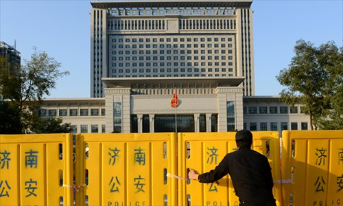 A man erects a barricade outside the Shandong Higher People's Court in Jinan, East China's Shandong Province on Thursday, in preparation for Friday's ruling on the appeal of Bo Xilai, former Chongqing Party chief.  Bo was sentenced to life in prison in September for bribery, embezzlement and abuse of power at the Jinan Intermediate People's Court.  Photo: AFP