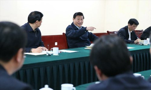 Xi Jinping (C), general secretary of the Communist Party of China (CPC) Central Committee and chairman of the CPC Central Military Commission, listens to reports by local authorities about poverty-alleviation work after his arrival in Fuping County, north China's Hebei Province, Dec. 29, 2012. Xi made a tour to impoverished villages in Fuping County from Dec. 29 to 30, 2012.   Photo: Xinhua