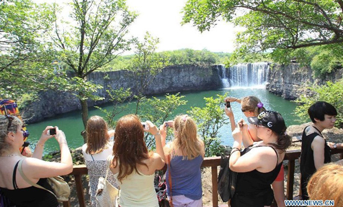 Russian visitors take photos of the Diaoshuilou Waterfall at the Jingpo Lake scenic area in Mudanjiang, northeast China's Heilongjiang Province, July 7, 2012. About 30 percent more tourists have visited the Jingpo Lake scenic area this year than the same period last year, following a series of promotions. Photo: Xinhua