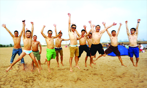 Employees from gay website danlan.org pose on the beach.