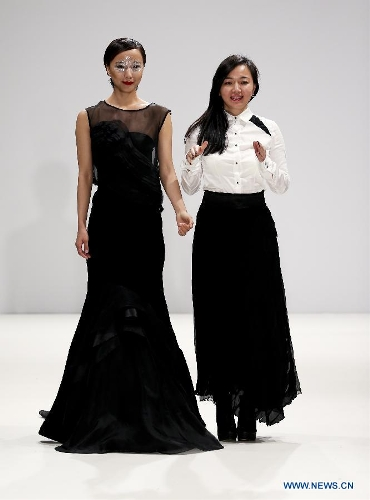 Chinese actress Wang Luodan (L) and Chinese designer Jenny Ji greet to audience after Jenny Ji's fashion show during London Fashion Week in London, Britain, on Feb. 18, 2013. (Xinhua/Tang Shi)