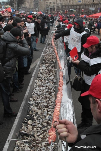 People grill a long shish kebab in Kiev, Ukraine, March 2, 2013. A 150.6-meter-long kebab was made in Kiev on Saturday. A total of 200 kg of meat and 800 kg of charcoal were used to make the kebab.(Xinhua/Sergey Starostenko)