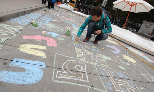 A man chalk-draws on the pavement during first Chalkupy Vancouver event in Vancouver, Canada, on September 22, 2012. People from all walks of life descend on Robson Street in downtown Vancouver at noon to create beautiful sidewalk chalk art together. Photo: Xinhua