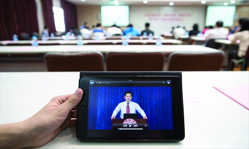 A university student watches an open course on a computer tablet in Shanghai on April 16, 2013. Photo: CFP