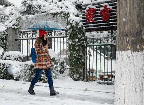A woman walks on a snow-covered street in Changchun, capital of Northeast China's Jilin Province, October 22, 2012. Most parts of Jilin witnessed snowfall on Monday. Photo: Xinhua