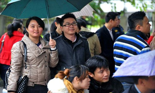 Couples wait in rain to register in front of the marriage registration office in Haikou, capital of South China's Hainan Province, January 4, 2013. Quite a number of couples flocked to tie the knot on January 4, 2013, or 2013/1/4, which sounds like