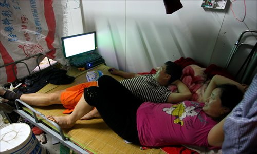 Henan native Ding, now a small labor contractor, plays computer games on a narrow bed while his wife watches closely.Photo: Yang Hui/GT