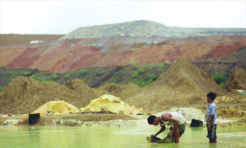 A Myanmese villager pans water for copper near the Sabal hill copper mine project in Monywa, northern Sagaing on September 14. Photo: AFP