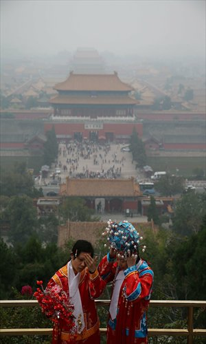 Two tourists wear traditional Chinese costumes to pose for pictures in Jingshan Park in Beijing on Sunday. The Forbidden City behind them is wrapped by heavy smog. Photo: Xinhua