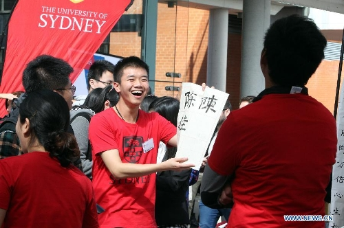 A student shows a calligraphy works during a gathering on the occasion of the Mid-Autumn Festival at the Sydney University, Sept. 8, 2014. The Mid-Autumn Festival, which falls on Sept. 8 this year, is a traditional Chinese festival for family reunions, during which folks will enjoy the full moon together and eat mooncakes. (Xinhua/Jin Linpeng)