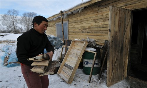 A Chinese man is carrying firewood to a dormitory where migrants from China live in Khakassia, Russia in February. Photo: CFP