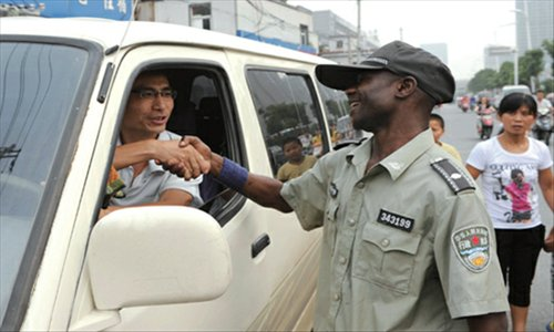 A foreign chengguan shakes hands warmly with a driver who has parked illegally and persuades him to move his car away.