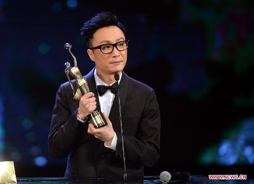 Actor Ronald Cheng holds the trophy after receiving the Best Supporting Actor award for his movie