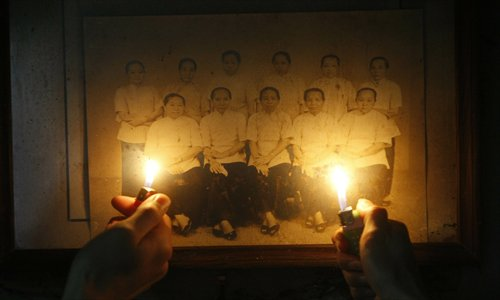 A group photo of zishunü is shown by lighter flames in a dark house built by returned zishunü in Gaobu township, Dongguan, Guangdong Province. Photo: CFP